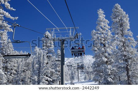 Skiers are riding a ski lift on a skiing resort at Lake Tahoe on a cold day after a snowstorm. - stock photo
