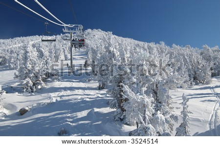 Skiers are riding a ski lift on a skiing resort at Lake Tahoe on a very cold day after a heavy snowstorm. Seats, cables a pillars are covered in frost. - stock photo