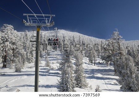Skiers are riding lift on a very cold day at one of the Lake Tahoe ski resorts (Sierra Nevada, USA). - stock photo
