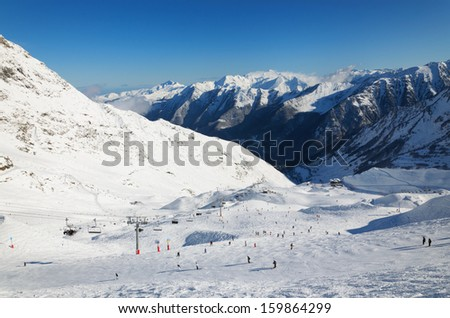 Skiers are sliding down snow-covered hill at the Cirque du Lys. There is range of mountains in the background. Winter Pyrenees is photographed at the Cauterets ski resort. - stock photo