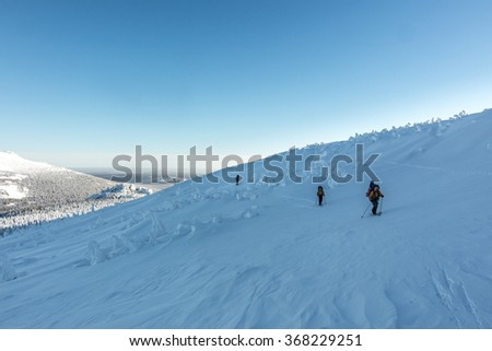 Skiers ascend the hill