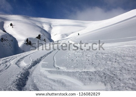 Skiers descend a large slope in the Utah mountains, USA.