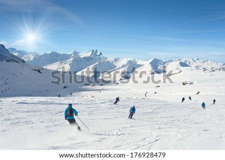 Skiers enjoy in the mountain on a sunny day, Val Thorens, France - stock photo