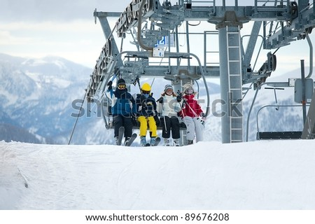 Skiers getting out the chair lift - stock photo