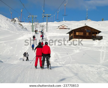 Skiers going uphill on a T-bar lift (Switzerland)