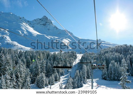 Skiers in a chairlift backlit against a  background of the mountains, forest and blue sky