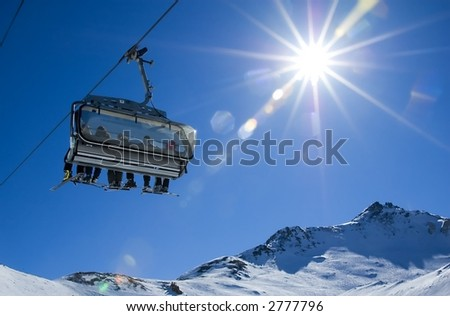 skiers in a chairlift backlit by the sun and spreading sunflares - stock photo