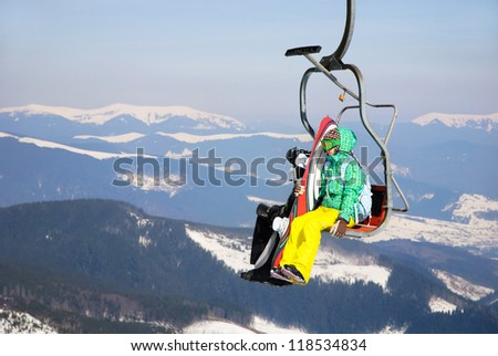 Skiers in mountains on a ski-lift