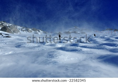 skiers on a glacier in very high winds which are blowing the snow in dense clouds