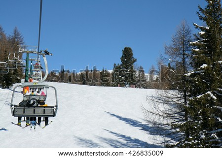 Skiers on a seat on the slopes. Val di Fiemme, Italy. Skiing on the dolomites