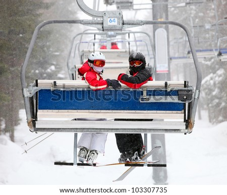 Skiers on a ski-lift - stock photo