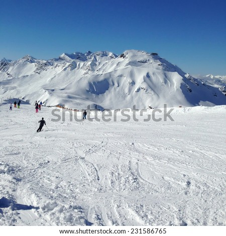 Skiers on a ski slope with mountains in background - stock photo