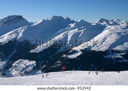 Skiers on a slope, mountains in the background. Taken in Davos, Switzerland. - stock photo