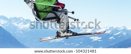 skiers on chairlift with snowy mountains in the background