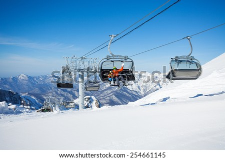 Skiers on the chairlift ropeway winter resort - stock photo