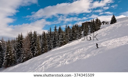 Skiers on the ski slopes of the Olympic. Ski slopes alpine peaks covered with snow. Skiers ride on groomed slopes, near the highway are growing spruce. December 29, 2010: Austria, the Alps - stock photo