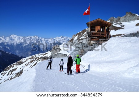 Skiers on the way to ski slope in Swiss Alps in sunny day. Small wooden house with red swiss flag near by ski slope. Swiss mountains and skiing resort in  Walliser Alps, Switzerland. - stock photo