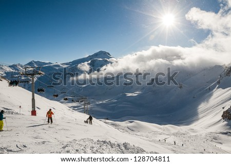 Skiers riding down the mountain to the sunny valley - stock photo