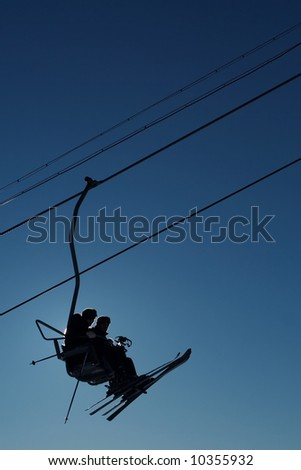 Skiers silhouette on cableway - stock photo