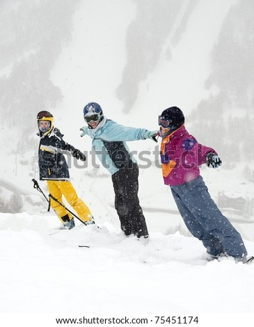Skiers standing in the falling snow