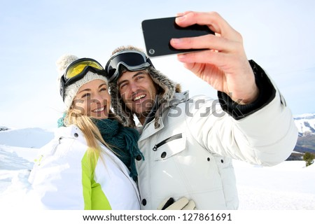 Skiers taking picture of themselves with smartphone - stock photo
