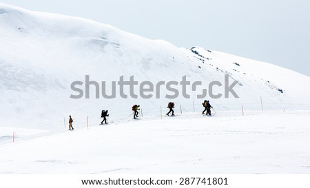 Skiers walking on snow covered mountain ranges, Tateyama, Japan - stock photo