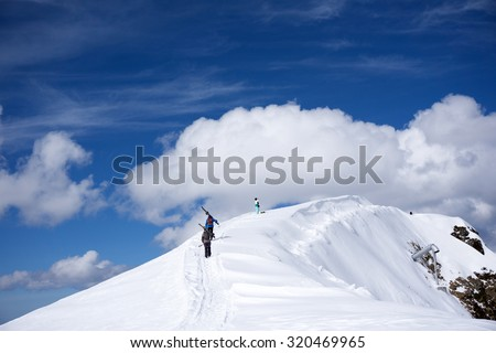 Skiers walking uphill for freeride, extreme sport - stock photo