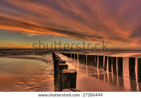 Skies after sunset at beach with breakwater structure HDR