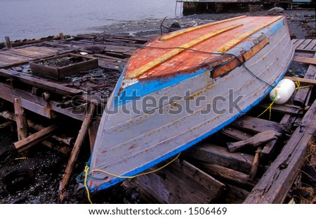 skiff boat lays hull up on dock for repair