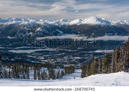 Skiing down to Whistler village from Blackcomb Mountain  - stock photo