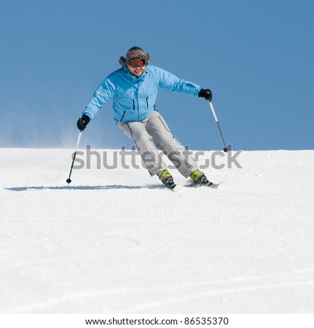 Skiing downhill - male on ski slope (space for text) - stock photo