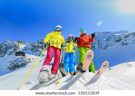 Skiing family enjoying winter vacation on snow in sunny cold day in mountains and fun. Switzerland, Alps