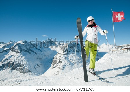 Skiing in Swiss Alps - portrait of happy female skier - stock photo