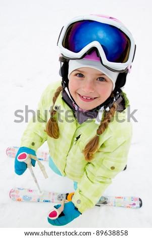 Skiing, portrait of cute skier on ski slope - stock photo