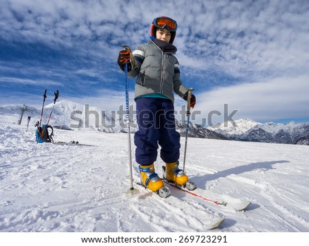 Skiing, portrait of young kid skier on ski slope - stock photo