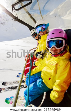 Skiing, ski lift, ski resort - happy skiers on ski lift - stock photo