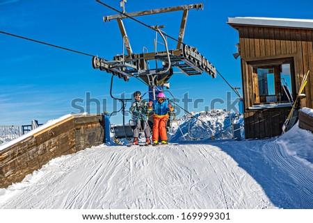 Skiing, ski lift - skiers on ski vacation - stock photo