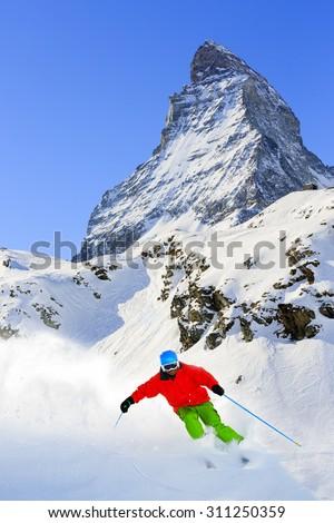 Skiing, Skier, Freeski, Freeride in Zermatt - man skiing downhill in fresh powder snow  - stock photo