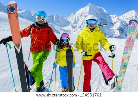 Skiing, skiers, sun and fun - family enyoing winter vacation - stock photo