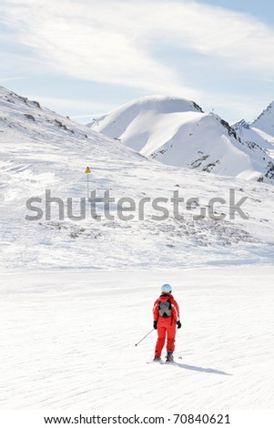 Skiing tourist in winter snow mountain landscape with blue cloudy sky. Red ski wear. Alps. France. - stock photo