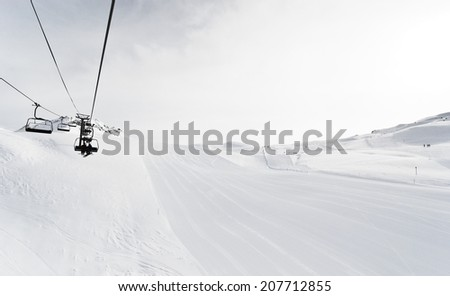 skiing tracks and ski lift on snow slopes of mountains in Paradiski region, Val d'Isere - Tignes , France - stock photo