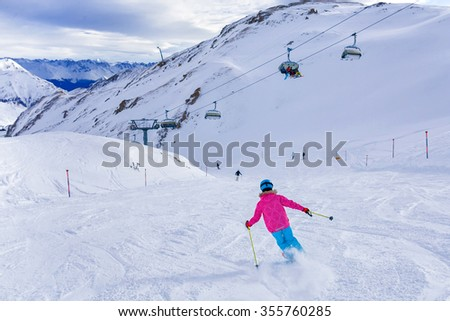 Skiing, winter, child - back view of young skier girl in helmet and goggles in winter resort - stock photo
