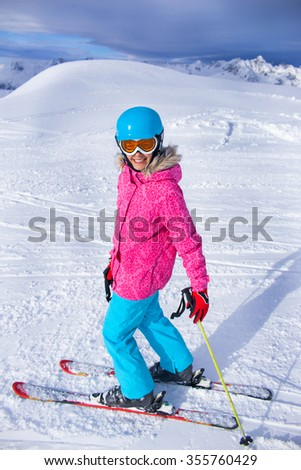 Skiing, winter, child - young skier girl in helmet and goggles in winter resort - stock photo