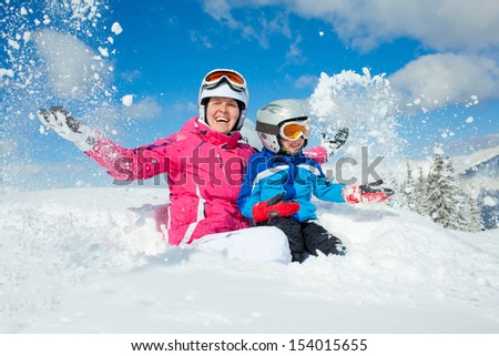 Skiing, winter, family - smiling boy in ski goggles and a helmet with his mother playing in snow in winter resort - stock photo
