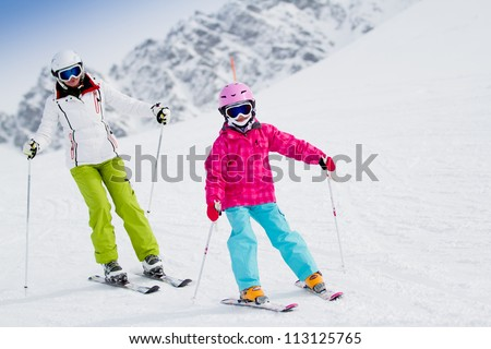Skiing, winter, ski lesson - kid with mother on mountainside - stock photo