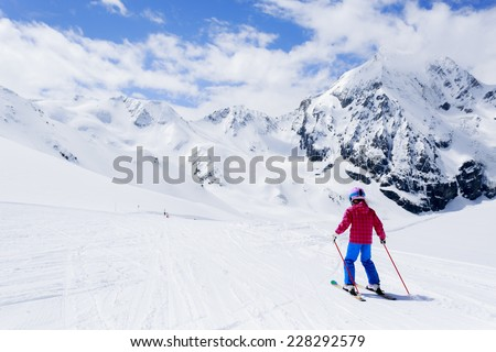 Skiing, winter sport, ski lesson - skier on mountainside - stock photo