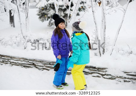 Skiing, winter sports - two adorable kid girls in colorful clothes have fun on perfect winter day - stock photo