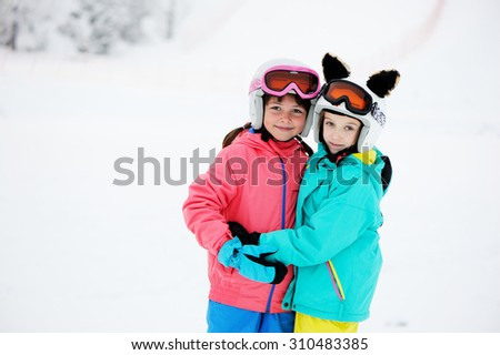 Skiing, winter sports - two adorable kid girls in helmets