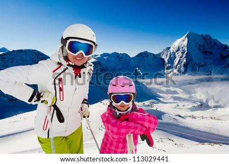 Skiing, winter vacation - portrait of happy skiers, mother and kid - stock photo