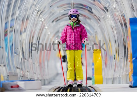 Skiing, young skier on ski lift, ski moving walkway - stock photo